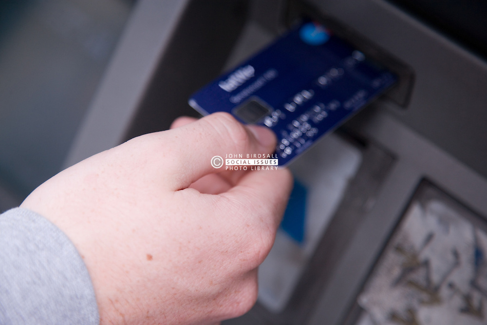 Young person withdrawing cash from an ATM,