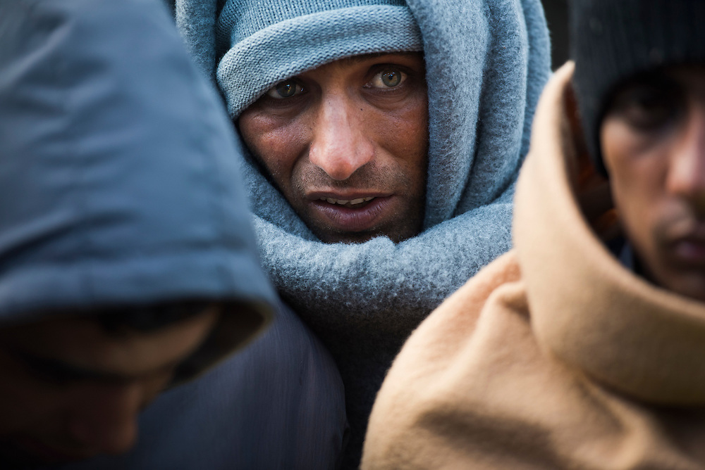 Pakistani refugees huddle together to stay warm while announcements are made by aid workers about changing conditions and policies at Better Days for Moria Refugee camp on March 16, 2016 near Moria, Greece.