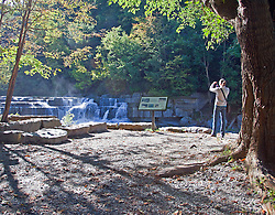 Girl photographing lower falls on Taughannock Creek, a pleasant entrance to Taughannock Falls State Park in New York State.  This is not the official falls, just a beautiful place in and of itself.  The creek empties into Cayuga Lake, one of New York's famed Finger Lakes.<br />