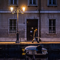 A man with a fishing rod walks on the Gran Canale in Trieste, Italy