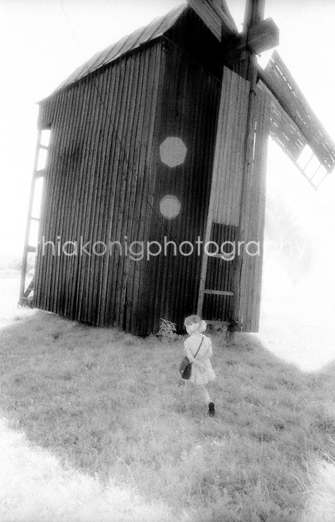 A little girl runs in the shadow of a Ukrainian windmill, Russia, USSR.
