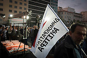 An Athenian holds a flag whilst listening to Fotis Kouvelis for the Left wing Democratic party in Athens, Greece. Image © Angelos Giotopoulos/Falcon Photo Agency