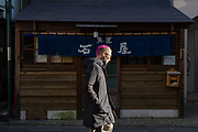 A young Japanese man, with a pink Mohawk haircut, walks past a small reastuarant in an old, wooden building  in Matsubara, Setagaya, Tokyo, Japan. Friday January 11th 2019