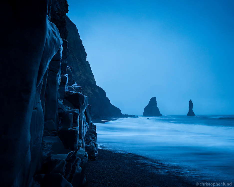 Reynisfjara black sand beach on the south coast of Iceland. Reynisdrangar sea stacs in background. January morning twilight.