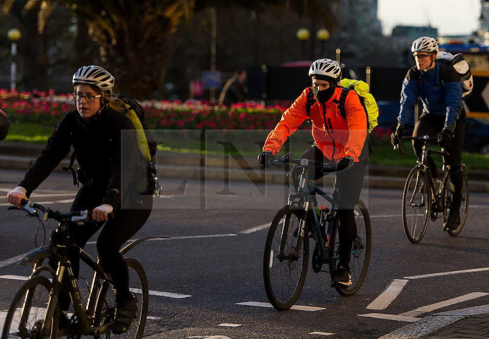 © Licensed to London News Pictures. 28/01/2016. London, UK. Commuters wrapped up as they cycle to work in warm sunshine cast over Westminster on a clear day at sunrise in London on a cold winter morning. Photo credit: Ben Cawthra/LNP
