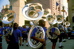 Stock photo of members of a marching band with tubas participating in a downtown Houston parade.
