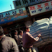 Dandong city, China, 11-2003..North Korean traders shop for daily neccessities to bring into North Korea, just across the border...China help North Korea fight the Korean War in the 1950s and continue to have a defence treaty with the Stalinist country...Ruled by the messianic leader Kim Il Sung and his son Kim Jong Il since 1948, North Korea has stubbornly stuck to its juche (self-reliance) ideology and siege mentality, imposing one Stalinist economic plan after another. Floods, droughts and mismanagement in the 1990s plunged the country into a preventable famine, killing up to three million, or 13 percent of the population. It now depends heavily on Chinese aid...