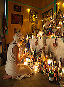 Vodou priestess Sallie Ann Glassman prays before the white altar at her temple in New Orleans, Louisiana