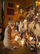 Vodou priestess Sallie Ann Glassman prays before the white altar at her temple in New Orleans, Louisiana