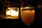 Candlelight illuminates a mixed drink.