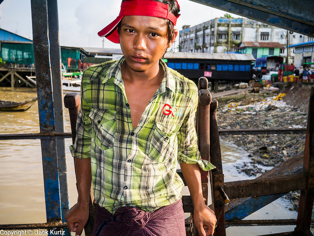 17 JUNE 2013 - YANGON, MYANMAR:  A porter waits for a customer in a large Yangon fish market. The market serves both domestic retail customers and wholesale international customers. With thousands of miles of riverine waterways and ocean coastline Myanmar has a large seafood and fishing industry.     PHOTO BY JACK KURTZ