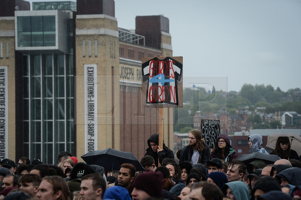 © Licensed to London News Pictures. 05/06/2017. Newcastle Upon Tyne, UK. Supporters wave homemade signs as they wait to hear from Jeremy Corbyn MP, Leader of the Labour Party, to address hundreds of his supporters who waited in the rain to hear him speak outside the Sage in Gateshead. Mr Corbyn spent one of the final days of the campaign trail in the Labour heartlands of North-East England before voters go to the polls in the UK General Election on June 8th 2017. Photo credit: MARY TURNER/LNP