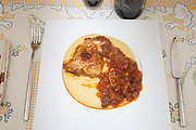 chicken cacciatore on polenta  view from above close-up on white dish and on rustic tablecloth background,italian traditional  food