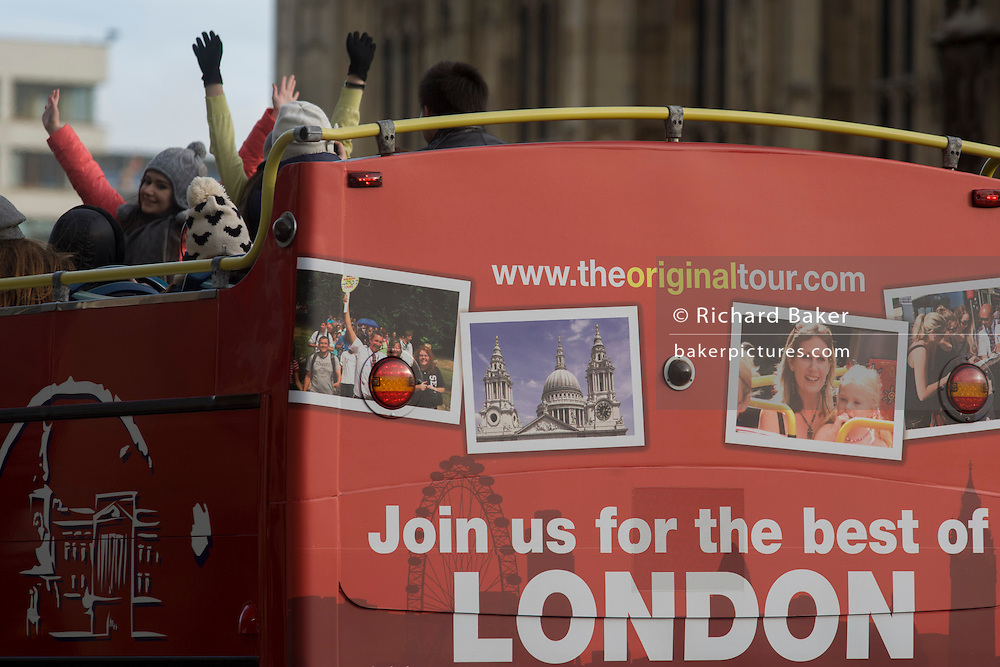 Rear of London tour bus and tourists with arms up.