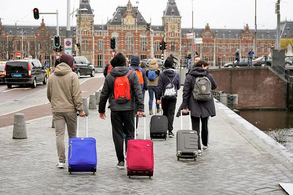 Nederland, the Netherlands, 13-3-2018Een groepje jonge manlijke toeristen, mannen, lopen met hun koffers naar het centraal station .Foto: Flip Franssen