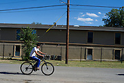 A boy rides his bike past the Ivy Apartments where Thomas E. Duncan, the first confirmed Ebola virus patient in the United States, was staying with family in Dallas, Texas on October 3, 2014. Duncan is now being treated at Texas Health Presbyterian Hospital Dallas while members of his family have been isolated in the apartment. (Cooper Neill for The New York Times)