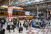 Passengers traveling through the Brighton side concourse of London Victoria railway, United Kingdom.  The train station is located in central London and is the second-busiest terminus in the country.