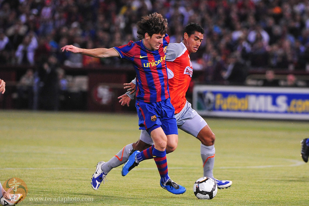 August 8, 2009; San Francisco, CA, USA; FC Barcelona forward Lionel Messi (10, left) fights for the ball with Chivas de Guadalajara midfielder Patricio Araujo (5, right) during the first half in the Night of Champions international friendly contest at Candlestick Park.
