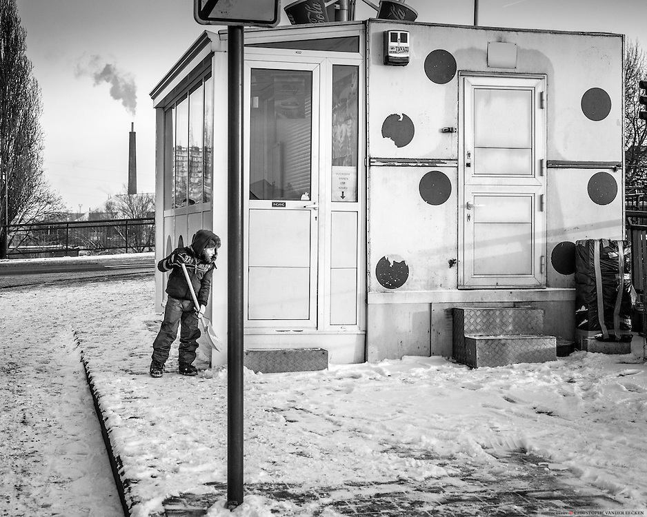 A young boy helps his mother with removing the snow in front of her fritshop