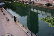 Two businessmen look out over the landscaped ponds in London' Barbican.