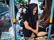 24 OCTOBER 2017 - BANGKOK, THAILAND: One of the first people in line at the gate into Sanam Luang and the royal cremation site. People started camping out along Atsadang Road in Bangkok near the royal cremation site on Monday. The gates won't open until Wednesday morning and the cremation isn't until Thursday night, so most people will sleep outside, on sidewalks and footpaths for three nights. Hundreds of thousands of people are expected to try to get into Sanam Luang, the site of the cremation of Bhumibol Adulyadej, the Late King of Thailand, but the site will only hold about 60,000 people. The Thai government has built replica crematoriums around Bangkok to accommodate the overflow crowds.        PHOTO BY JACK KURTZ