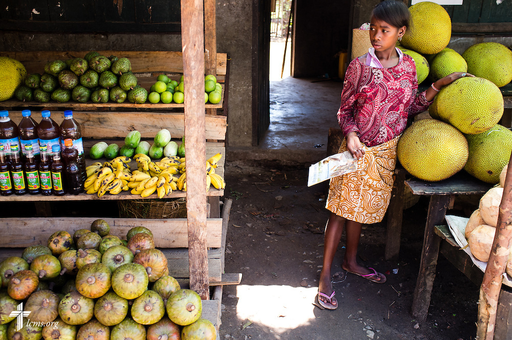 A girl sells fruit and vegetables on Monday, Oct. 20, 2014, at a roadside stand between Taolagnaro and Amboasary in rural southern Madagascar.  LCMS Communications/Erik M. Lunsford