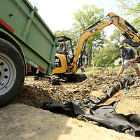 Thomas and Adrian Sanchez and Denny Waite, employees with Tupelo Parks and Recreation, work on a drainage and irrigation system on the west side of the walking track at Robins Field on Thursday.