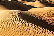 Sahara desert sand dunes with dark shadows at Erg Lihoudi, Morocco.