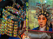 "26 NOVEMBER 2014 - BANGKOK, THAILAND: A Chinese opera performer checks her headdress in a mirror at the Chow Su Kong Shrine in the Talat Noi neighborhood of Bangkok. Chinese opera was once very popular in Thailand, where it is called ""Ngiew."" It is usually performed in the Teochew language. Millions of Chinese emigrated to Thailand (then Siam) in the 18th and 19th centuries and brought their culture with them. Recently the popularity of ngiew has faded as people turn to performances of opera on DVD or movies. There are about 30 Chinese opera troupes left in Bangkok and its environs. They are especially busy during Chinese New Year and Chinese holidays when they travel from Chinese temple to Chinese temple performing on stages they put up in streets near the temple, sometimes sleeping on hammocks they sling under their stage.      PHOTO BY JACK KURTZ"