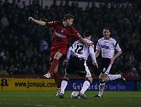 John Macken (centre) shields the ball from Colchester defender John White (left). Steve Howard watches (right)