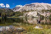 Hiker on the shore of Big Pine Lake #4, John Muir Wilderness, Sierra Nevada Mountains, California USA