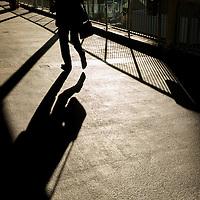China, Hong Kong, Shadow of man walking at sunrise across pedestrian bridge at Admiralty Centre above Connaught Road on winter morning