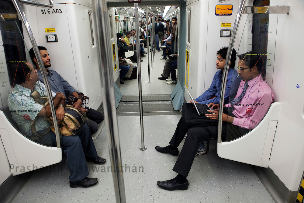 """Passengers travel inside a metro train from the Central Secratariat station using the """"Yellow Line"""" route of the Delhi Metro network in New Delhi, India, on Friday, October 22, 2010. Photographer: Prashanth Vishwanathan/HELSINGIN SANOMAT"""