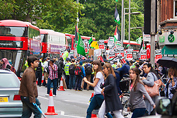 "London, July 5th 2014. Shoppers cross the street while in the background hundreds protest near the Israeli embassy in London against the ongoing occupation of Palestine and the west's support of ""Israel's collective punishment of Palestinians""."