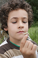 Boy (7-9) holding caterpillar outdoors