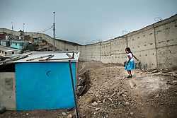 NO WEB/NO APPS - (Text available) A little girl plays next to the 'Wall of shame' (Muro de la Verguenza) which divides the Districts of Santiago de Surco and San Juan de Miraflores in the city of Lima, Peru in May 2017. In Peru's capital Lima, a three-meter-high concrete wall topped with reels of razor wire separates two areas. The so-called 'Wall of Shame' - sometimes nicknamed 'Peru's Berlin Wall' - divides the urbanisation of Las Casuarinas, where some of the country's richest inhabitants live, and the poor suburb of Vista Hermosa next door. It was initially put up over fears that the inhabitants from the poor neighbourhood would steal from wealthy fellow citizens living nearby. On the rich side of the wall, the price for a square meter can exceed 2,000 dollars. To enter the area, you must show your ID to the guards watching the gate at the bottom of the hill. Former high-ranking politicians and bank directors live here. Their houses are surrounded by lush gardens and swimming pools despite the scarcity of water. Meanwhile, on the San Juan de Miraflores side, residents often fall victim to robbery and theft. They live in houses of barely 25m², made from scrap material, surrounded by the sand and earth characteristic of Lima's desert landscape. Photo by Giacomo D'Orlando/ABACAPRESS.COM