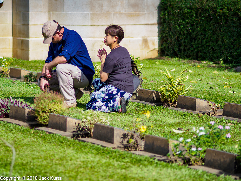 """11 NOVEMBER 2018 - KANCHANABURI, KANCHANABURI, THAILAND:  GARTH O'CONNELL, left from Australia, and his friend, SOKO TAMIKA, pray at the grave of O'Connell's great uncle, an Australian aboriginal soldier, killed working on the """"Death Railway"""" and buried in the Kanchanaburi War Cemetery in Kanchanaburi, Thailand, during Rememberance Day observations. Kanchanaburi is the location of the infamous """"Bridge On the River Kwai"""" and was known for the """"Death Railway"""" built by Japan during World War II using allied, principally British, Australian and Dutch, prisoners of war as slave labor. There are 6,982 people buried in the cemetery, including 5,000 Commonwealth soldiers and 1,800 Dutch soldiers. November 11, 2018 marked the 100th anniversary of the end of World War I, celebrated as Rememberance Day in the UK and the Commonwealth and Veterans' Day in the US.    PHOTO BY JACK KURTZ"""