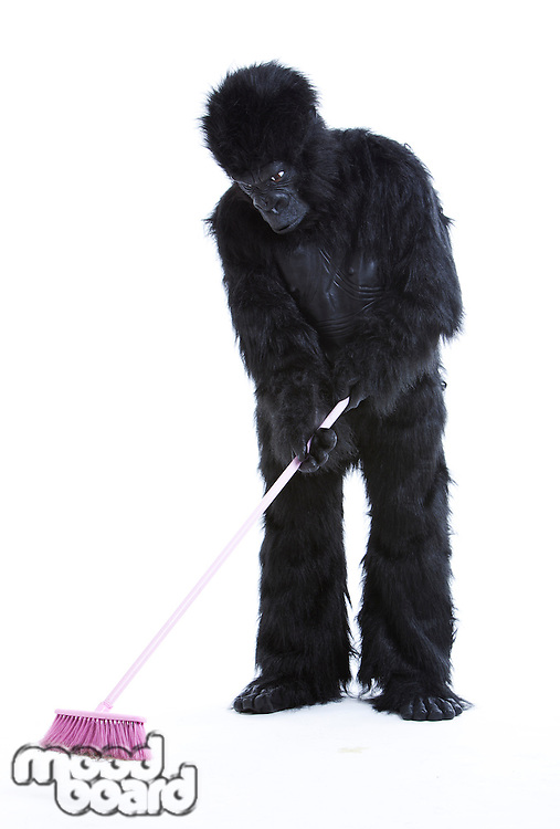 Young man in gorilla costume sweeping the floor over white background