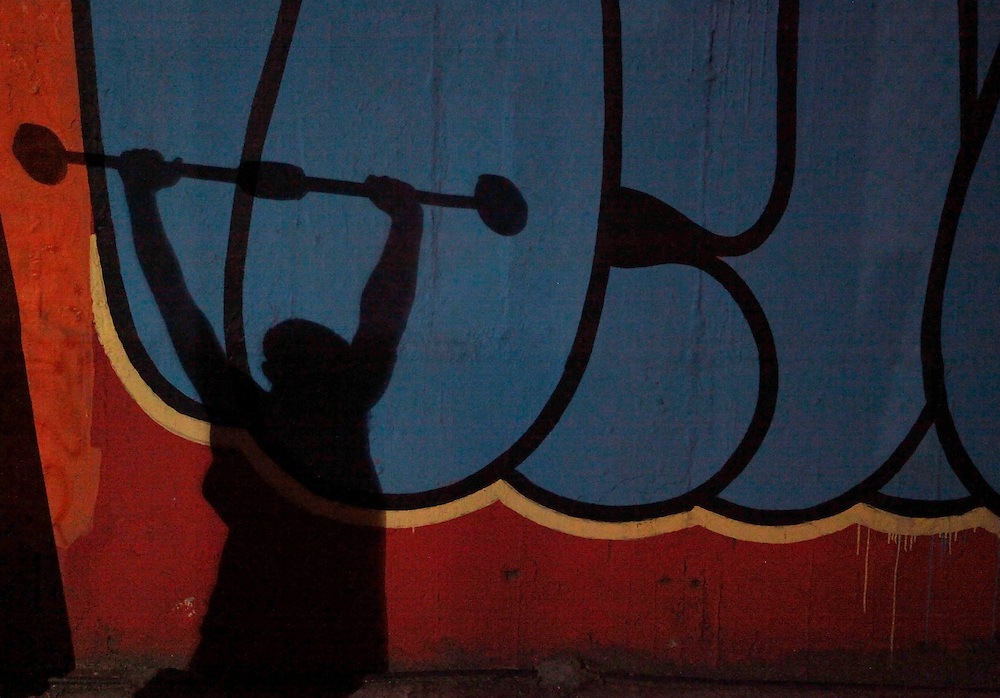 The shadow of aspiring boxer Laercio is projected on a wall as he uses a discarded truck axle for weight training at a gymnasium under the Alcantara Machado viaduct in the Mooca neighborhood of Sao Paulo, March 28, 2011. The Boxing Academy of Garrido, founded by Brazilian former pro boxer Nilson Garrido, adopts primitive training equipment that he developed himself during his years as a coach, in a project whose goal is to take the sport to the poor and marginalized population.