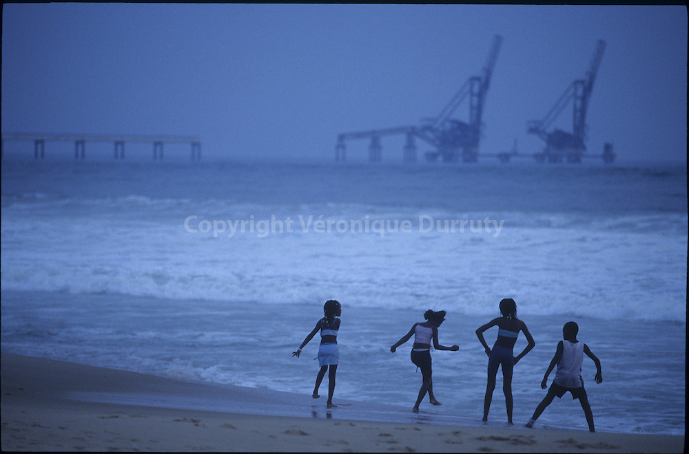 CHILDREN PLAYING ON THE BEACH, FACING OIL EQUIPMENT, POINTE  NOIRE, CONGO