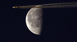 © Licensed to London News Pictures. 07/05/2018. Ditcheat, Somerset, a Lufthansa Passenger jet framed by the Moon lit by the rising sun   Photo credit: Jason Bryant/LNP