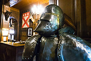 A suit of armor greets guests at Comlongon Castle, a restored Medieval Scottish tower house dating from the late 1400s. Overnight visitors can stay in the attached Edwardian hotel, a baronial style mansion built 1900-02, set in 120 acres of manicured gardens, sweeping lawns, carp pond, lakes and woodlands, near Clarencefield and Dumfries, in southwest Scotland, United Kingdom, Europe. Originally built by the Murrays of Cockpool, Comlongon Castle remained in the Murray family until 1984. The castle is 50 feet square and stands 70 feet high, with walls over 4 meters thick, with impressive displays of weapons, armor and banners.
