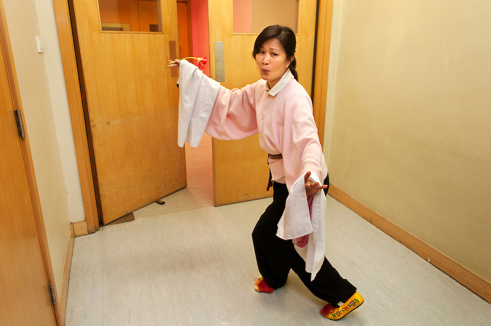 An amateur actress from a Shatin based company is rehearsing an opera excerpt in the entrance corridor of a practice hall
