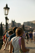 Czeck Republic - Prague, Young woman enjoys the the passing crowds and sun on the Charles Bridge