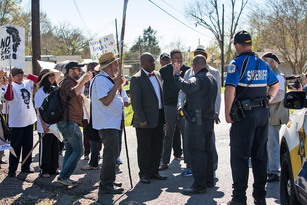 Police try to stop opponents of Entergy's Natural Gas Power Plant in New Orleans East before they march along River Road in Cancer Alley on March 3, 2018.  The march passed Entergy's Waterford 3 Nuclear Generating Station and  Dows Chemical Plant, ending at the Taft Cemetery.