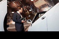Salesman standing in automobile showroom.