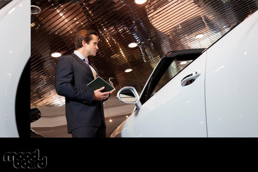 Salesman standing in automobile showroom.
