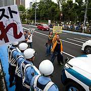 KAWASAKI, JAPAN - JUNE 05: Anti-racist man, block a police car from moving forward so that the fascist and racist groups who were trying to disrupt a counter-racist protest in Nakahara Peace Park, Kawasaki City, Kanazawa prefecture, Japan on June 5, 2016. A district court in Kanagawa Prefecture has issued a first-ever provisional injunction preventing an anti-Korean activist from holding a rally near the premises of a group that supports ethnic Korean people.<br /> <br /> Photo: Richard Atrero de Guzman