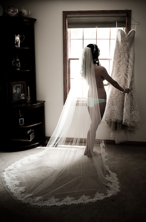 Boudoir bridal images help create a sense of both sexiness and purity as the bride admires her wedding gown.
