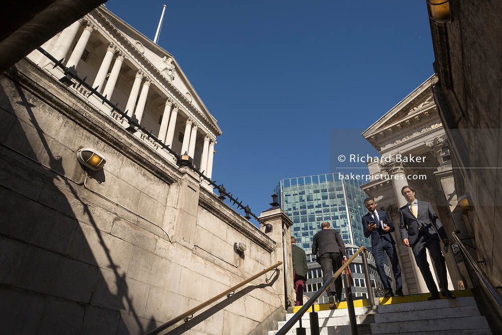 Businessmen descend the steps leading down into Bank Underground station, beneath the Bank of England and neo-classical pillars of Royal Exchange in the City of London - the capital's financial centre (aka The Square Mile), on 27th September 2018, in London, England.